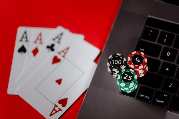 Poker cards, stacks of poker chips and laptop on a red background closeup.