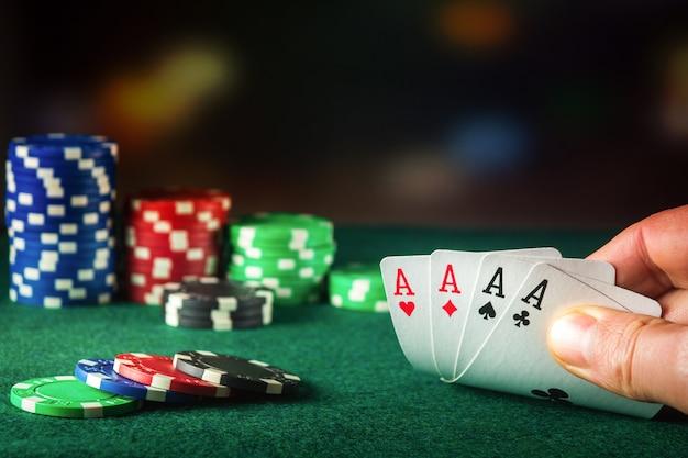 4種類またはクワッドの組み合わせのポーカーカード。ギャンブラーの手のクローズアップはポーカークラブでトランプを取ります