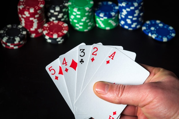 Карты для покера с высокой комбинацией карт крупным планом рука игрока держит игральные карты