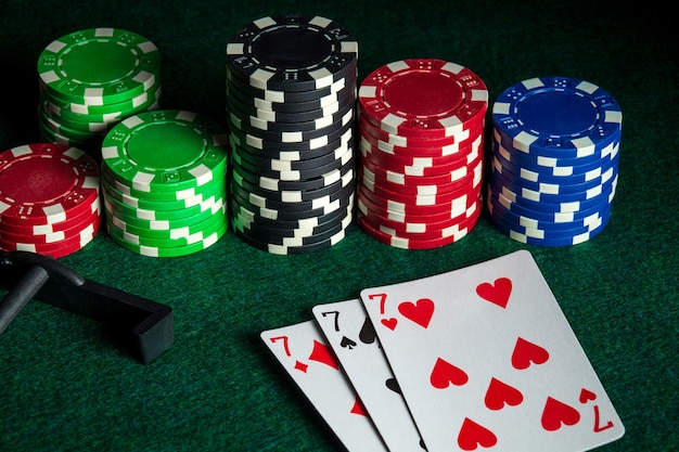 Poker cards with three of a kind or set combination in casino. chips and rake on the green table