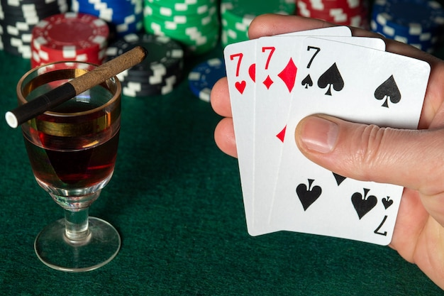 Poker cards with three of a kind or set combination close up of gambler hand keeps playing cards