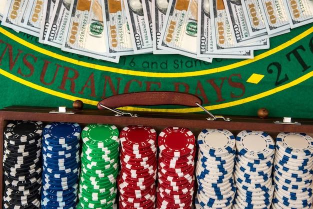 ゲームテーブルのケースにポーカーチップとドル。