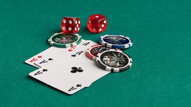 Покерные фишки, карты и кости на зеленом фоне концепция азартных игр и развлечений