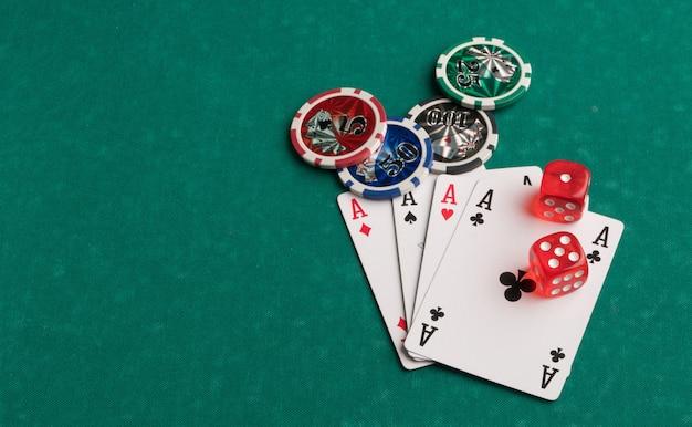緑の背景にポーカーチップカードとサイコロギャンブルとエンターテイメントの概念