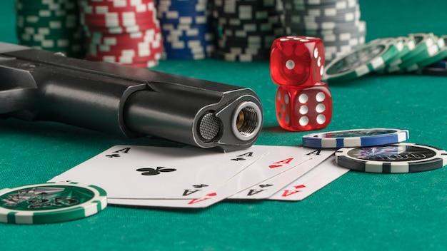 緑の背景にポーカーチップカードと銃ギャンブルとエンターテイメントカジノとポーカー