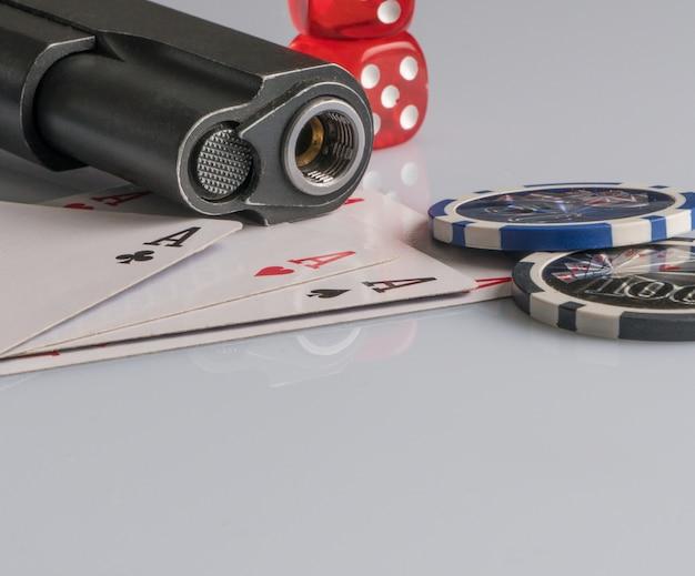 白い背景の上のポーカーチップカードと銃ギャンブルとエンターテインメントの概念