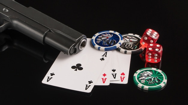 Poker chips cards and a gun on a black background the concept of gambling and entertainment
