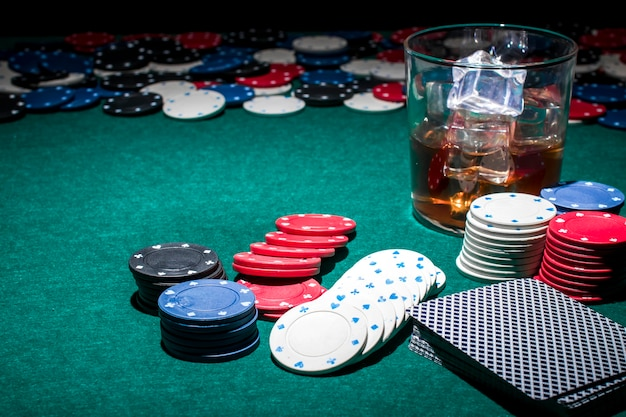 Poker chips and glass of whiskey on green poker table