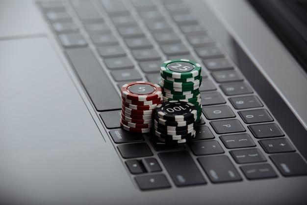 ラップトップのポーカーチップ。カジノのオンラインコンセプト。