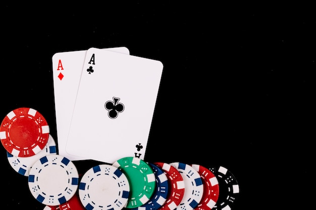 Poker chips and two aces playing cards on black surface