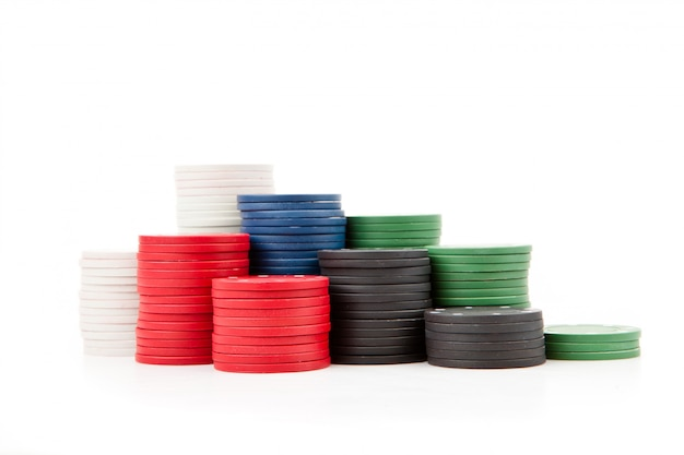 Poker coins piled up together against a white background