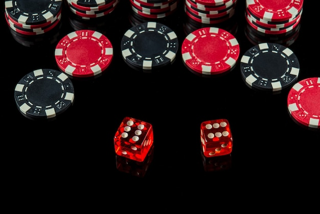 Poker dice with maximum winning combination of twelve on black table and chips in the background