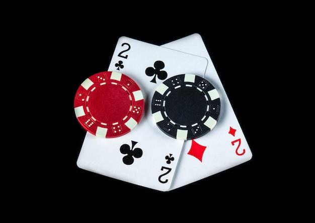 1ペアの組み合わせのポーカーゲーム。黒いテーブルの上のチップとカード。ポーカーでの賞金