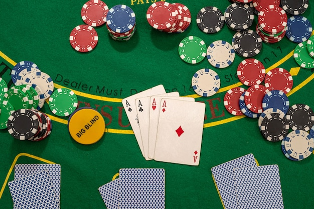 Poker play cards and chips on green table