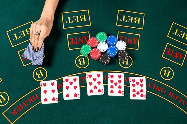 ポーカープレイ。プレイヤーの手札のチップ。上面図。女性の手がカードを持ち上げて見る