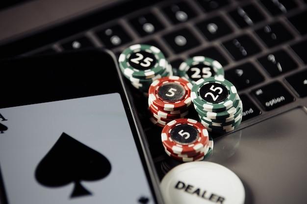 ポーカープレイオンラインコンセプト。ポーカーチップ、トランプ、キーボードのスマートフォン
