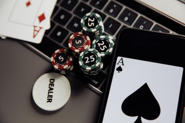 Играть в покер онлайн. фишки для покера, игральные карты и смартфон на клавиатуре