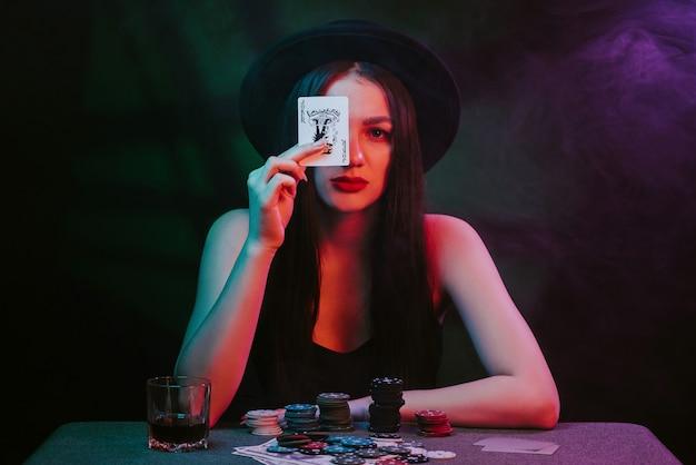 카드와 칩이 있는 카지노 테이블에서 포커 플레이어. 모자를 쓴 여자가 도박을 하고 있다