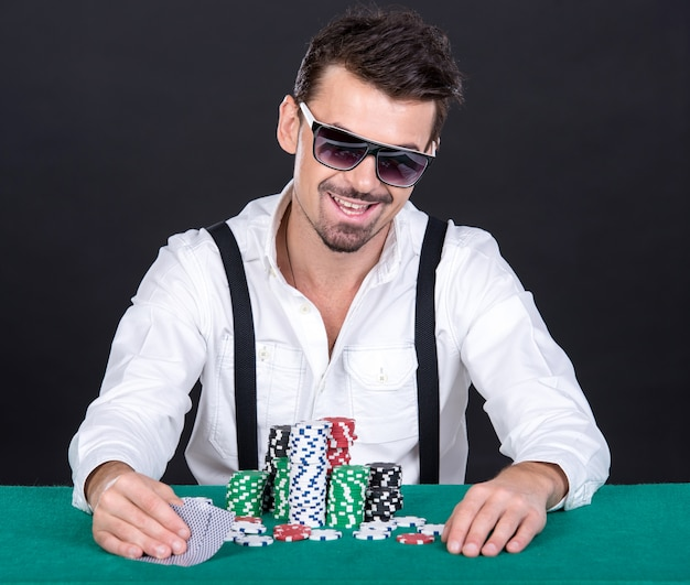 The poker player in black glasses, in a casino.