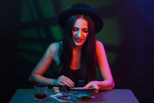 Poker player at a casino table with cards and chips. the woman in the hat is gambling