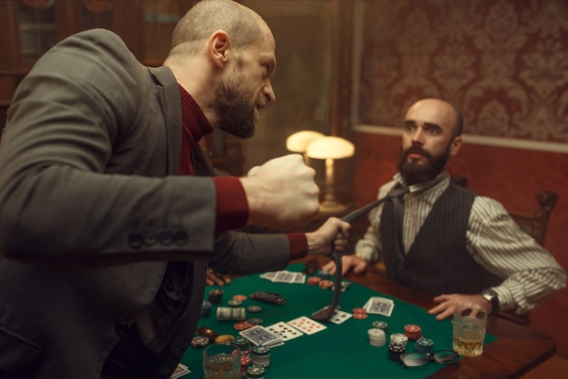 Poker player caught the sharper in casino, risk. games of chance addiction. men with whiskey and cigars in gambling house