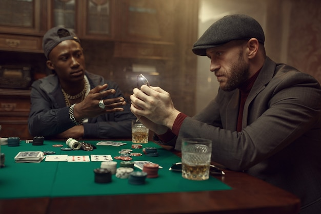 포커 플레이어는 그의 손목 시계를 은행에 둔다. 기회 중독, 위험, 도박장 게임. 위스키와 시가가있는 남성 레저