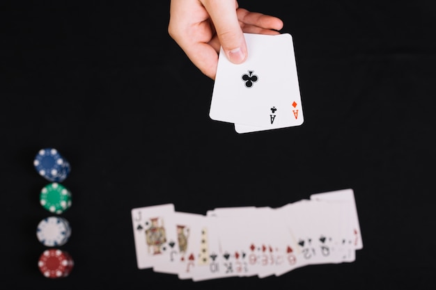 Poker player's hand holding playing cards on black backdrop
