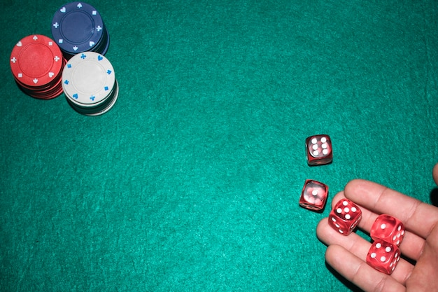 Poker player's hand throwing red dices on poker table