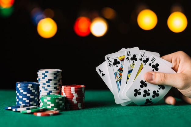 Poker player's hand with royal flush club near chips on green surface