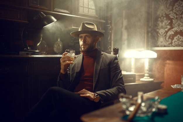 Poker player in suit and hat drinks whiskey in casino bar, risk addiction.