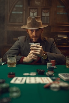 Poker player in suit and hat plays in casino, risk addiction.