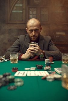 Poker player in suit plays in casino, risk addiction.