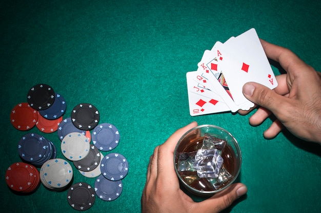 Poker player with whisky glass and royal flush card on poker table