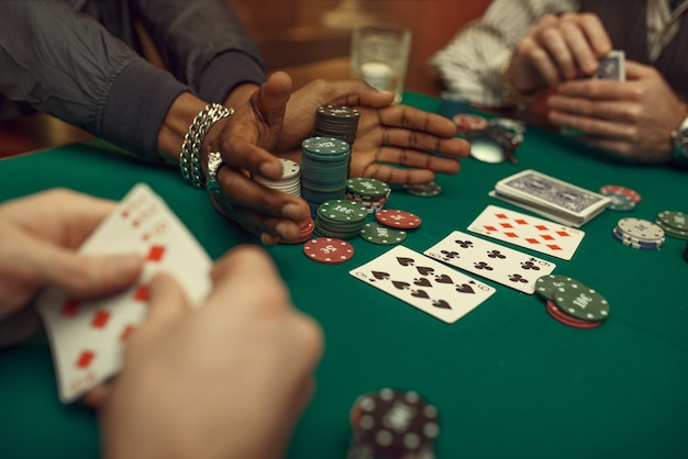 Poker players hands with cards, gaming table with green cloth in casino
