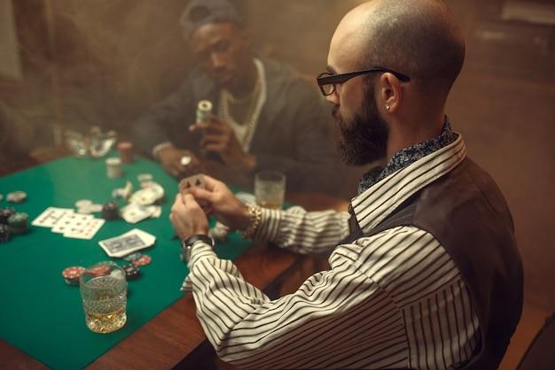 포커 플레이어는 카지노에서 녹색 천으로 게임 테이블에 돈을 베팅합니다. 중독, 위험, 도박장