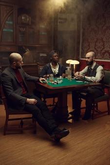 カジノでカードとチップを持っているポーカープレイヤー。中毒、ギャンブルの家