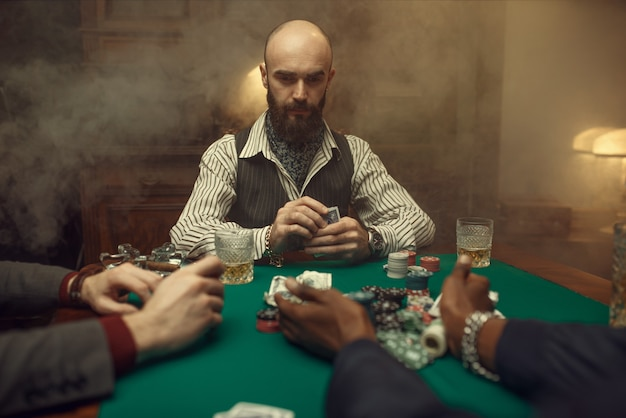 Poker players with cards and chips in casino. addiction, gambling house