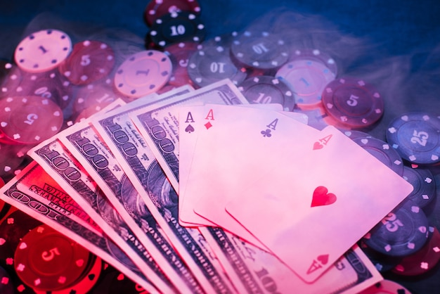 Poker playing chips, cards and money with puffed- up smoke