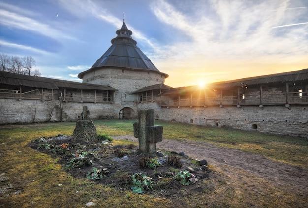 Покровская башня и древняя стена кремля в пскове и крест на земле в солнечный осенний день