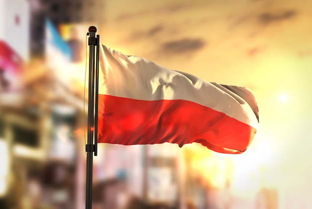 Poland flag against city blurred background at sunrise backlight