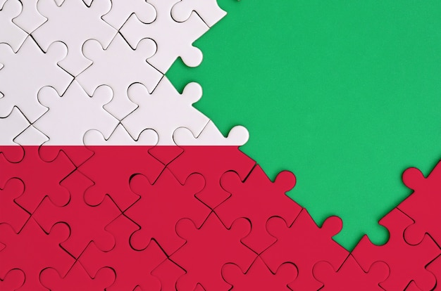 Poland flag  is depicted on a completed jigsaw puzzle with free green copy space on the right side