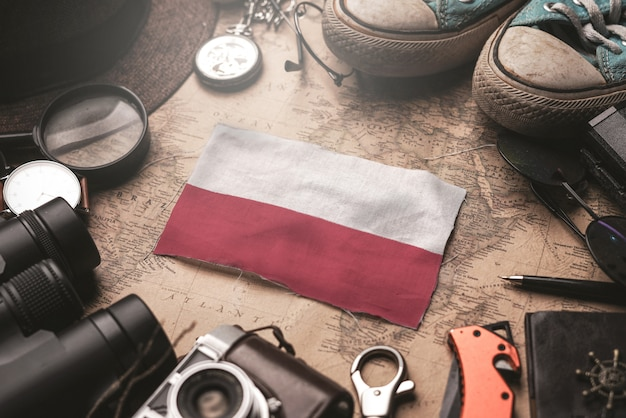 Poland flag between traveler's accessories on old vintage map. tourist destination concept.