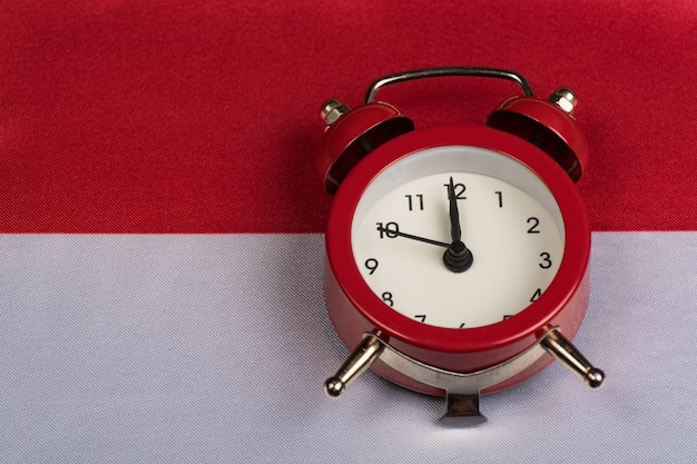 Poland flag and vintage alarm clock on close up.