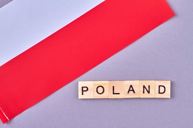 木製のブロックで書かれたポーランド。紫の背景に分離されたヨーロッパの国の国旗。