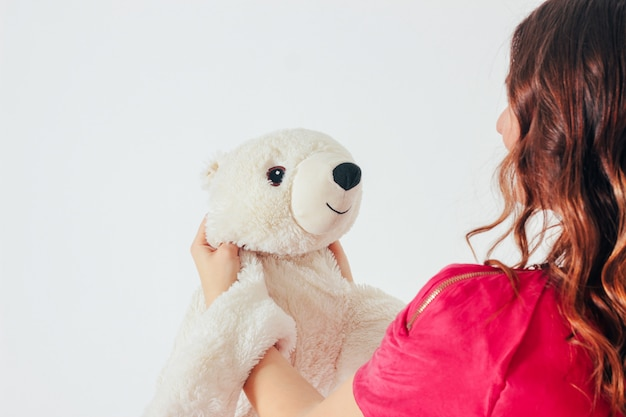 Polar bear toy on hands of young woman in bright pink dress