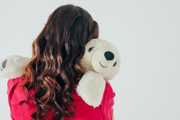Polar bear toy hugs young curly brunette woman
