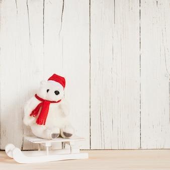 Orso polare con abiti natalizi su una slitta