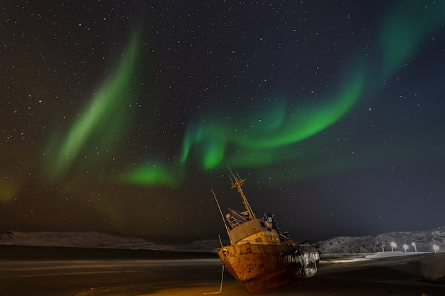Polar lights in the starry sky. a fishing boat lying on its side. teriberka, russia