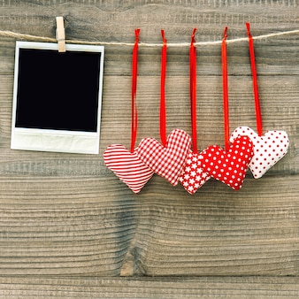 Polaroid photo frame and textile red hearts. valentines day concept