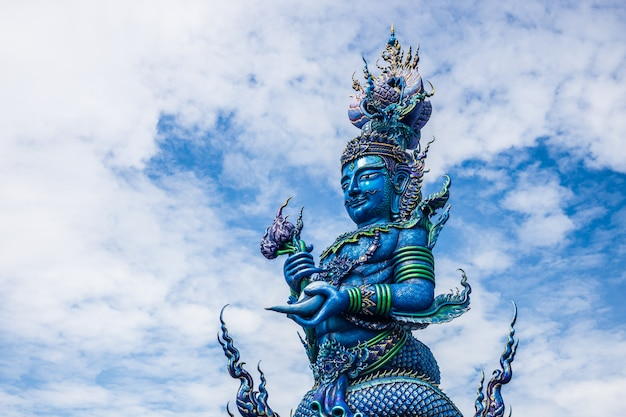 Pole carve of art fairy tale at wat rong sua ten temple with blue sky background